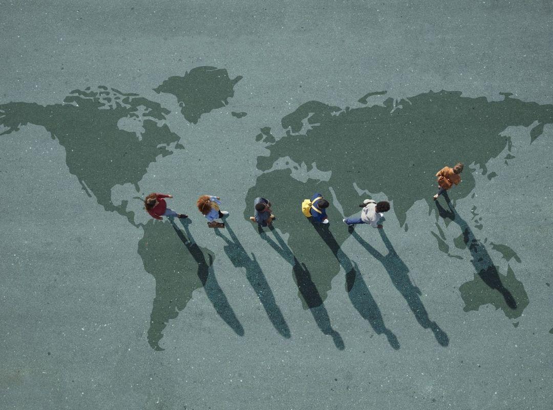 Menschen laufen in einer Reihe mit Abstand über eine Weltkarte