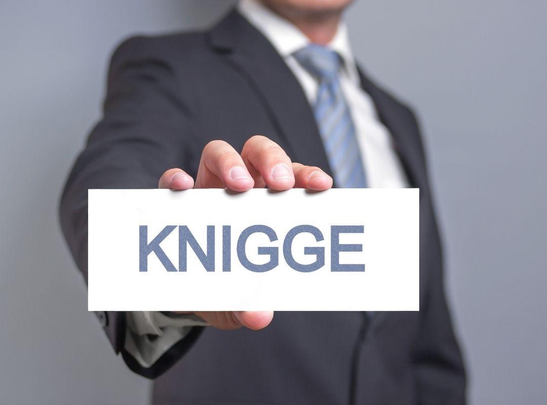 Geschäftsmann hält Knigge-Schild