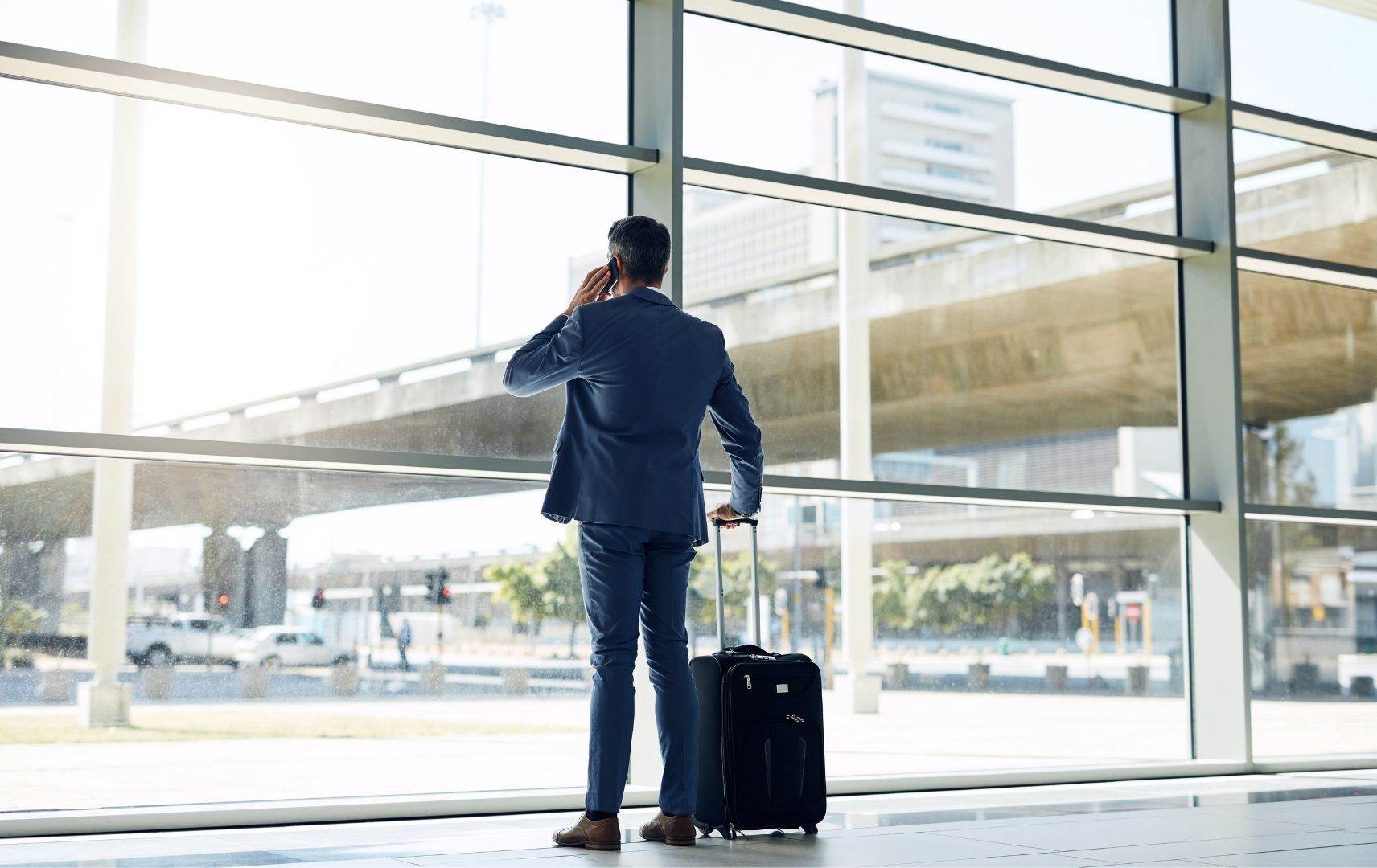Business Mann am Flughafen telefoniert