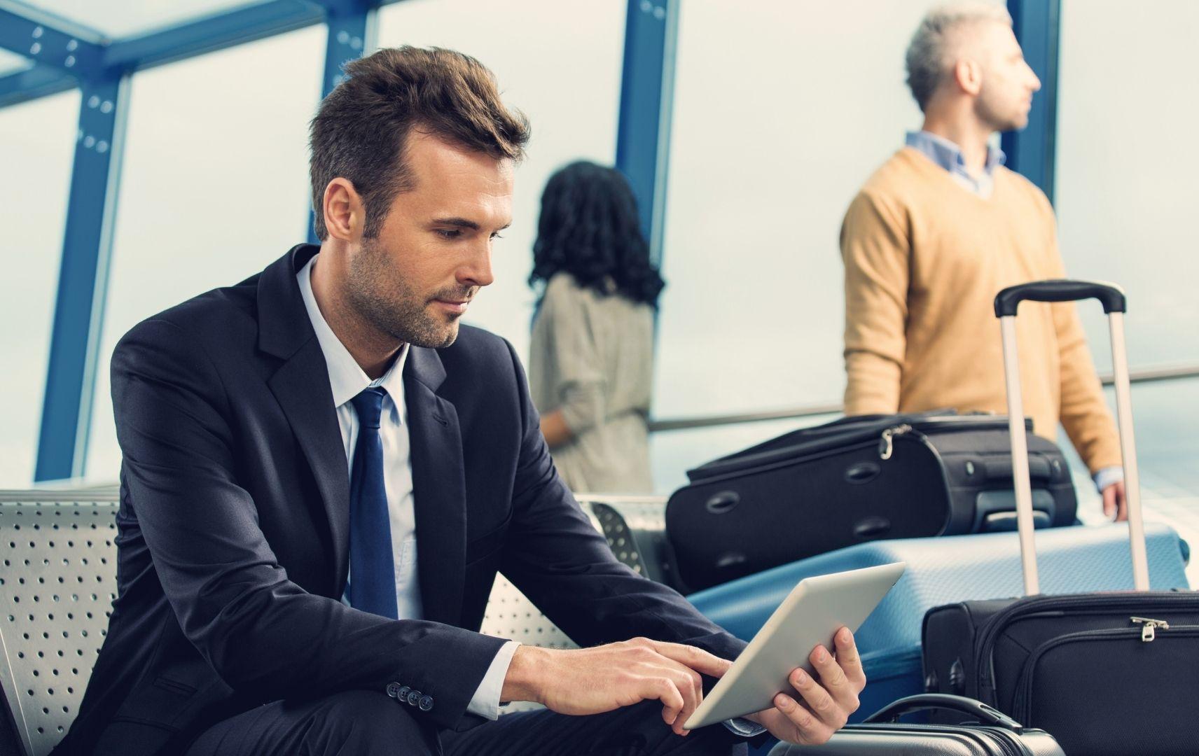 Business Mann sitzt am Flughafen mit Tablet