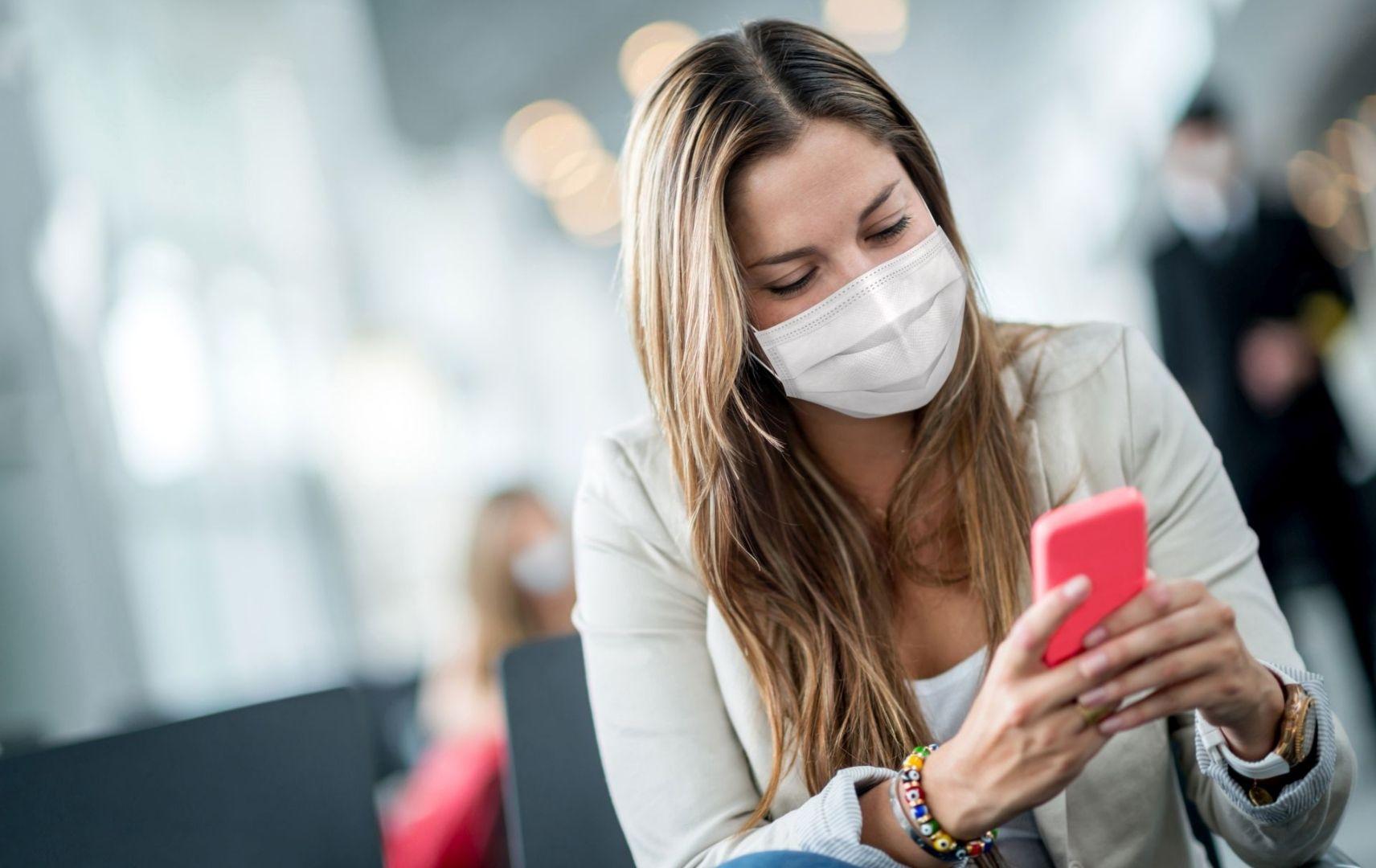 Frau mit Maske am Flughafen schaut auf ihr Mobiltelefon