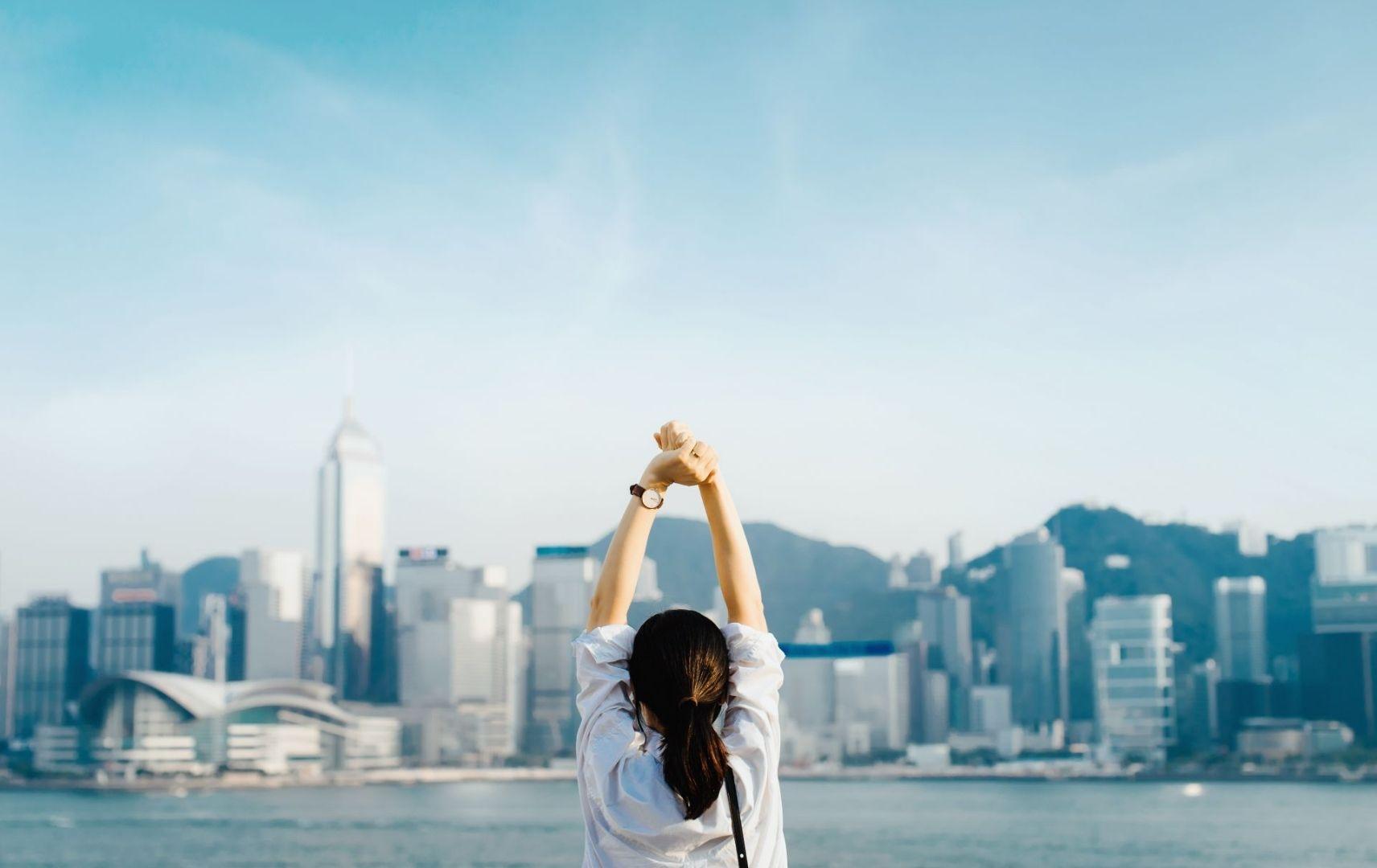 Frau streckt sich vor der Kulisse Hong Kongs