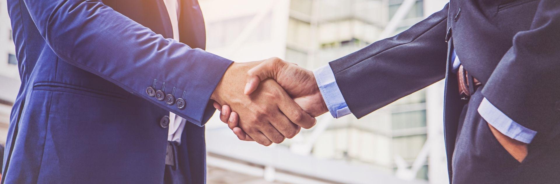 Geschäftsreise Reisebüro - Geschäftsmänner schütteln sich die Hände