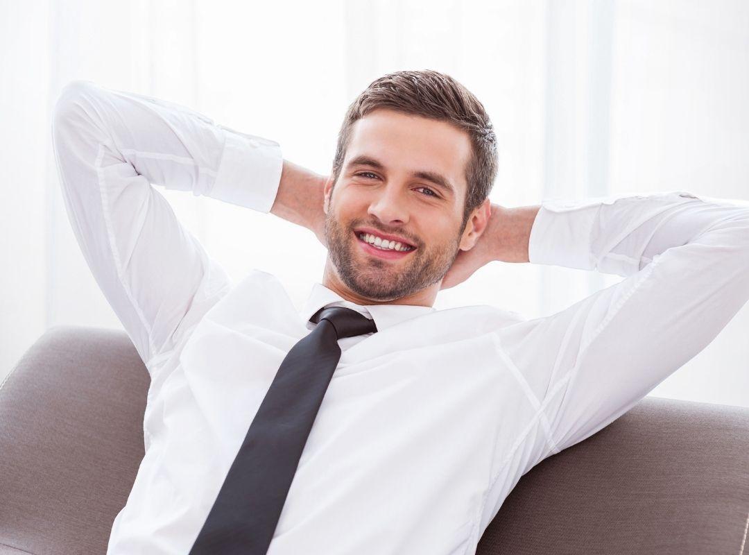 Junger Geschäftsmann lehnt sich entspannt zurück