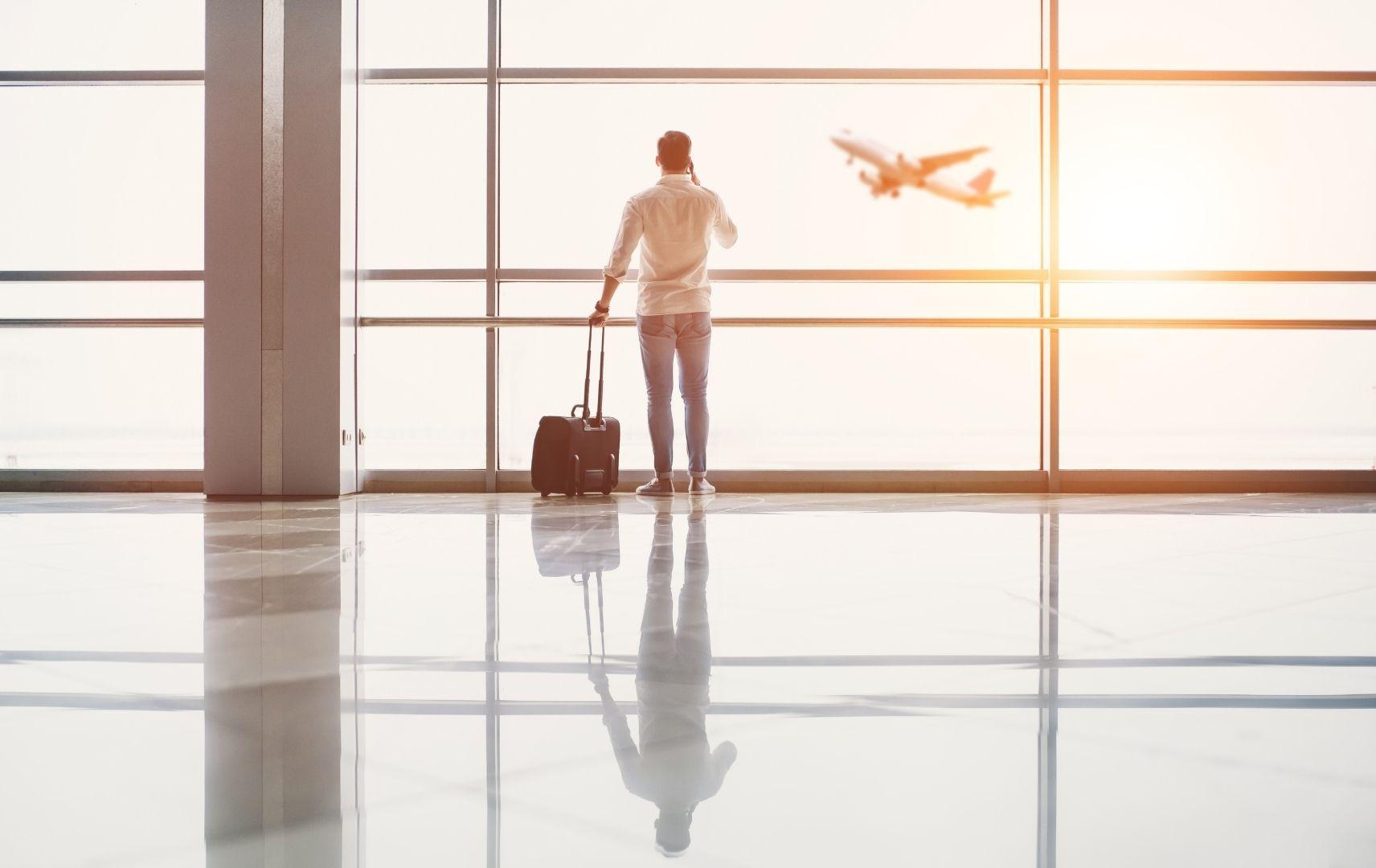 Mann am Flughafen mit Koffer