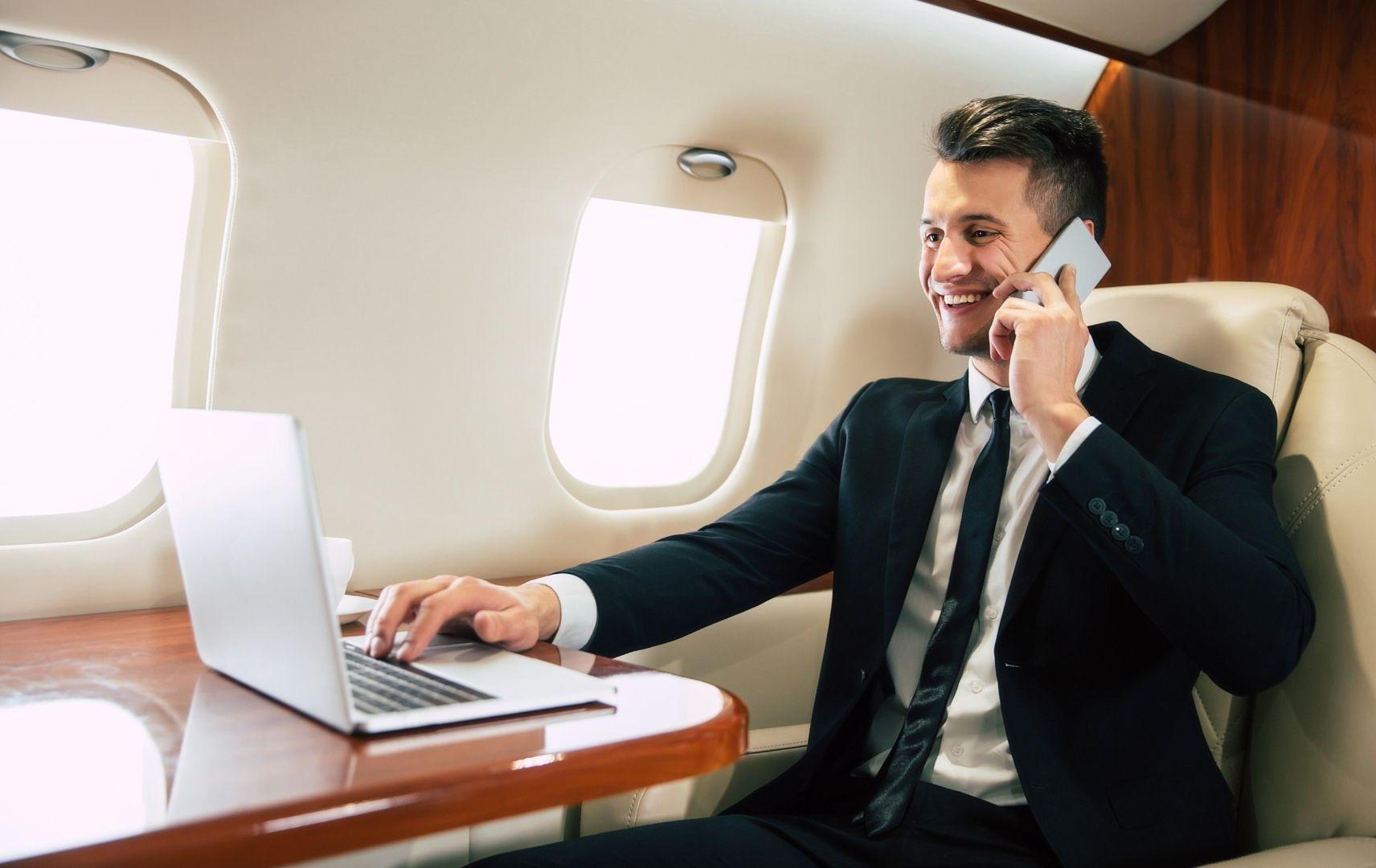 Mann am Laptop und Telefon im Flugzeug