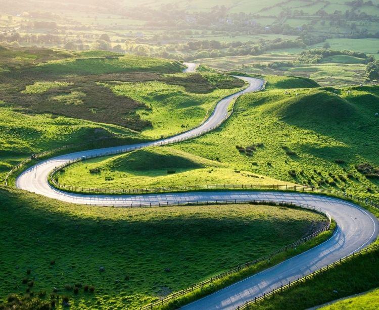 Eine leere Straße schlängelt sich durch eine grüne Landschaft