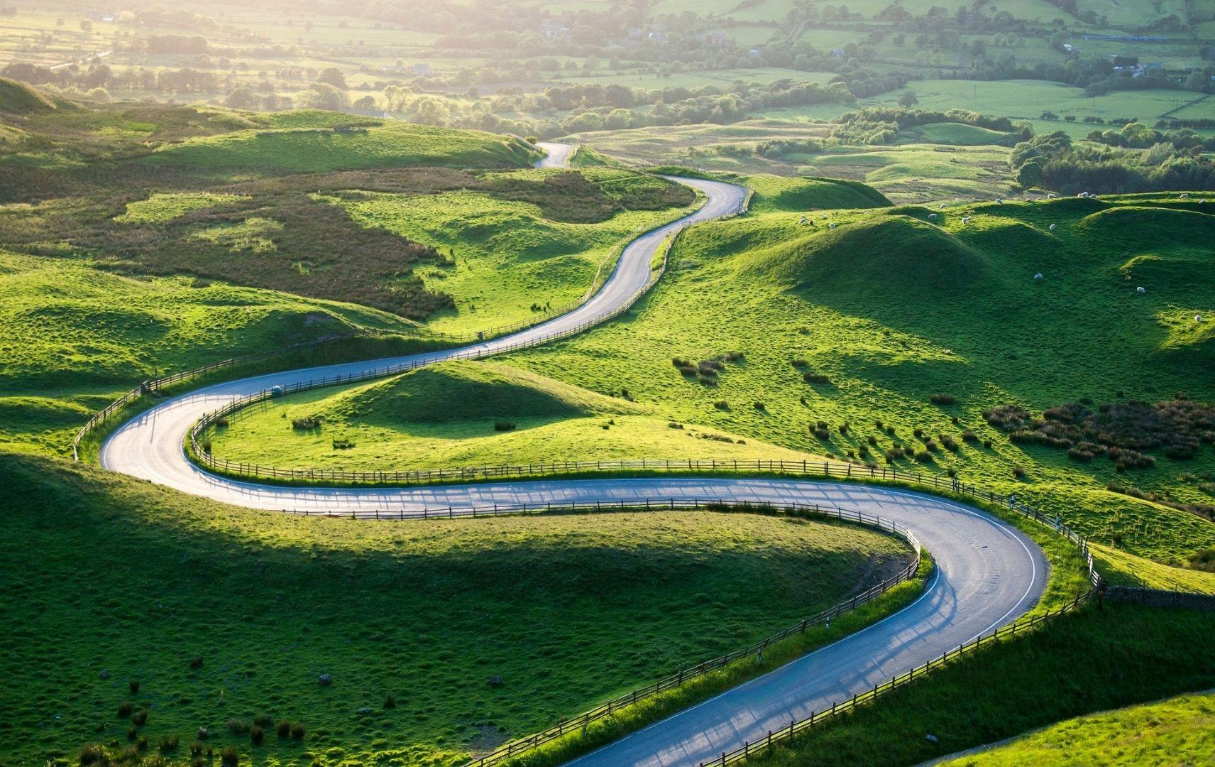 Leere Straße schlängelt sich durch grüne Landschaft