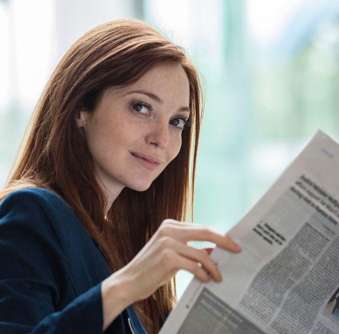 Junge Geschäftsfra liest eine Zeitung