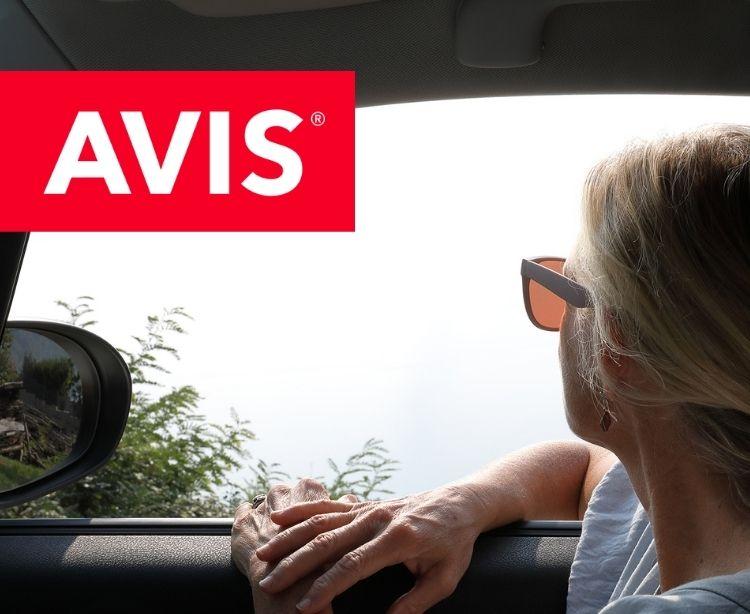 Avis -Frau im Mietwagen genießt die Landschaft