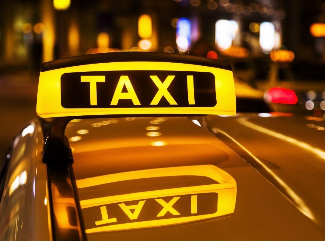 Gelbes Taxi mit leuchtendem Taxi-Schild