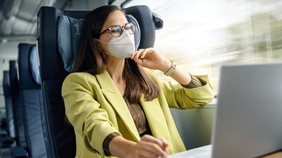 Deutsche Bahn Frau im Zug mit Maske und Laptop