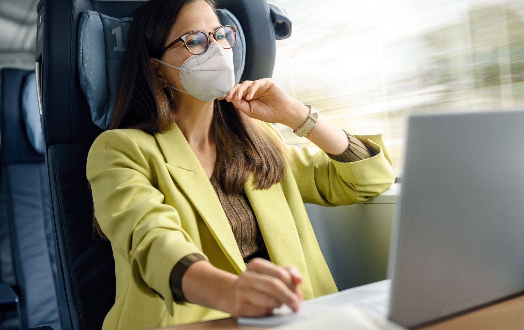 DB Business Reisende mit Maske und Laptop im ICE