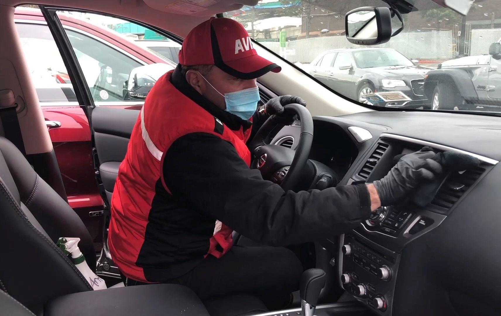 Avis Fahrzeugreiniger mit Maske und Handschuhen desinfiziert Mietwagen