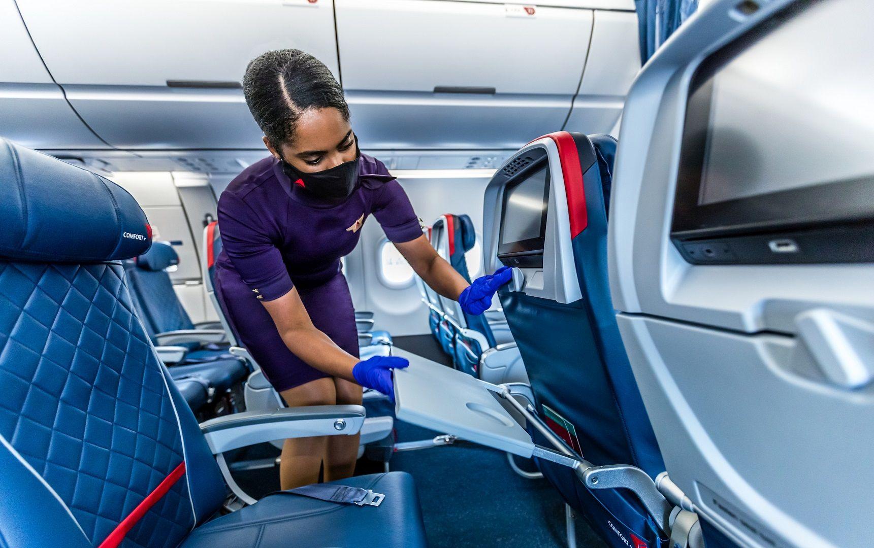 Flugbegleiterin mit Maske und Handschuhen an Bord von Delta Air Lines