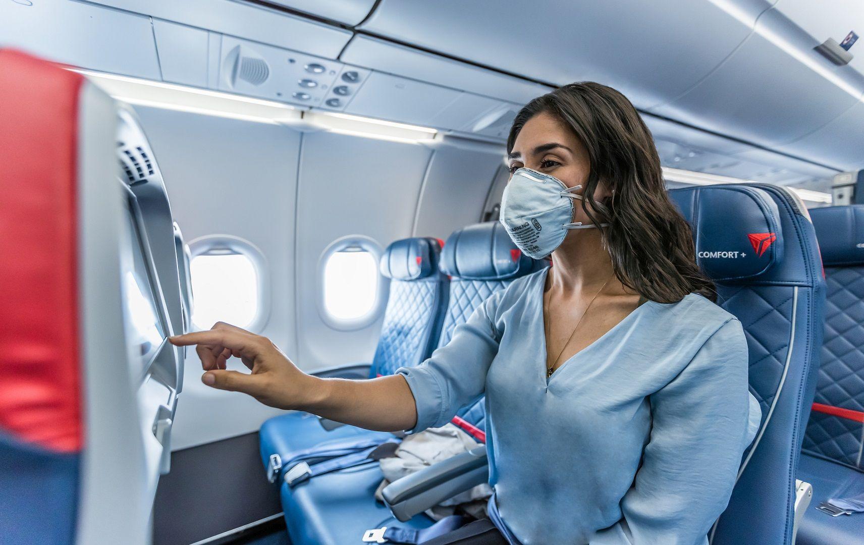 Kundin mit Maske an Bord von Delta