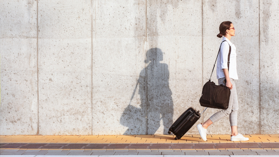 Young woman walking on a sidewalk beside the concrete wall and pulling a small wheeled luggage
