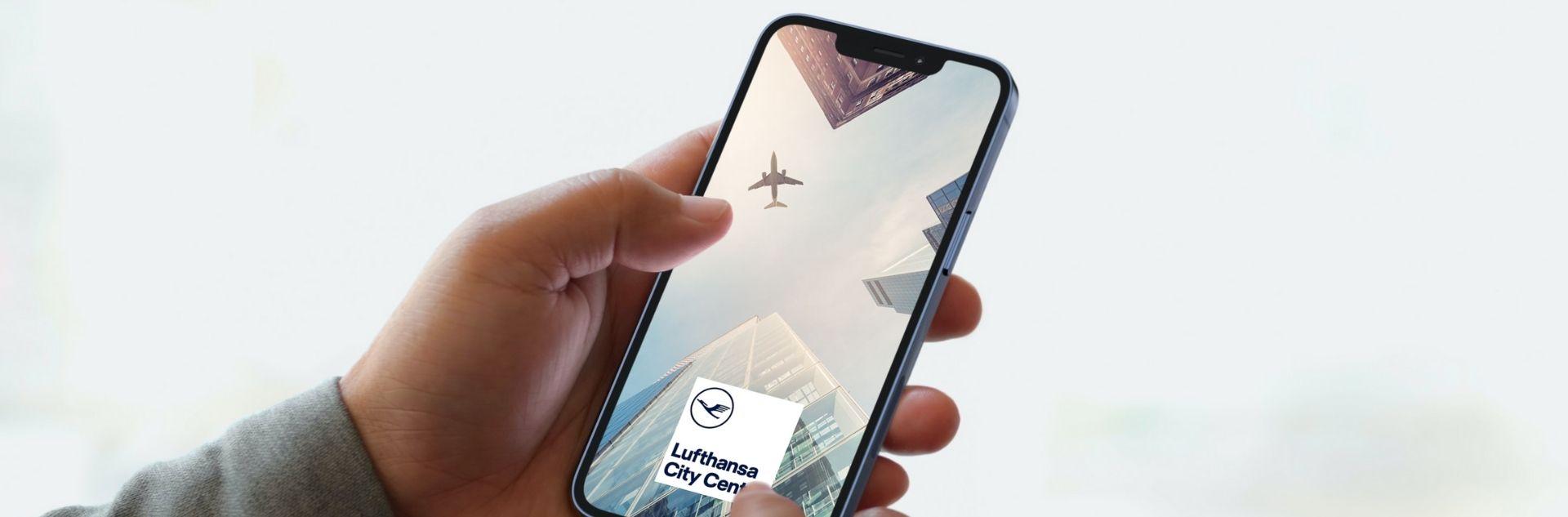 Hand mit Smartphone und LCC App auf dem Display mit Logo