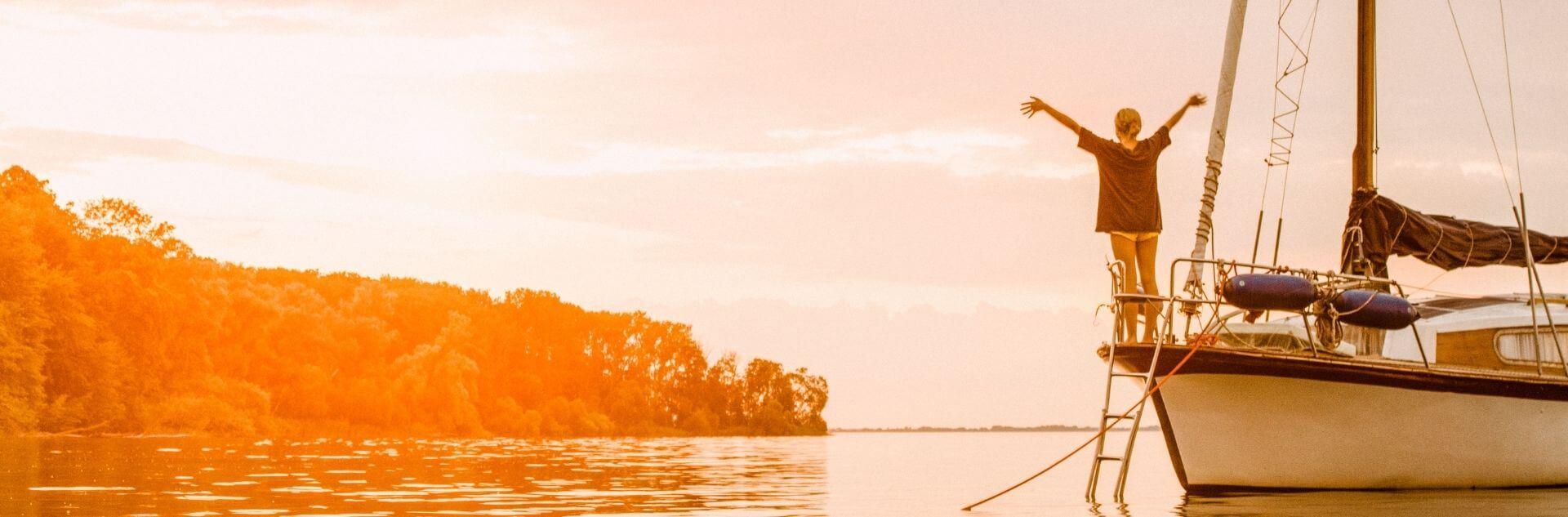 Frau schaut auf Sonnenuntergang auf einem Segelboot auf der Müritz