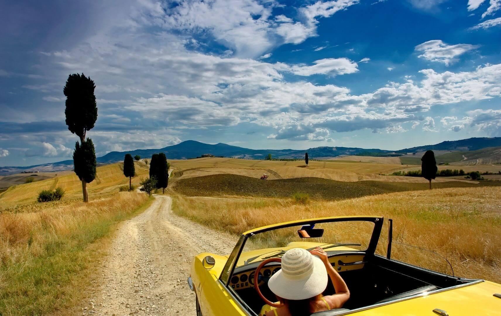 Frau fährt im Cabrio durch die Toskana