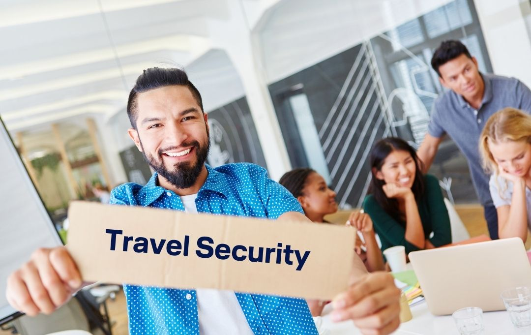 Mann mit hellblauem Hemd lächelt und hält ein Schild mit Aufschrift Travel Security, im Hintergrund Teamkollegen