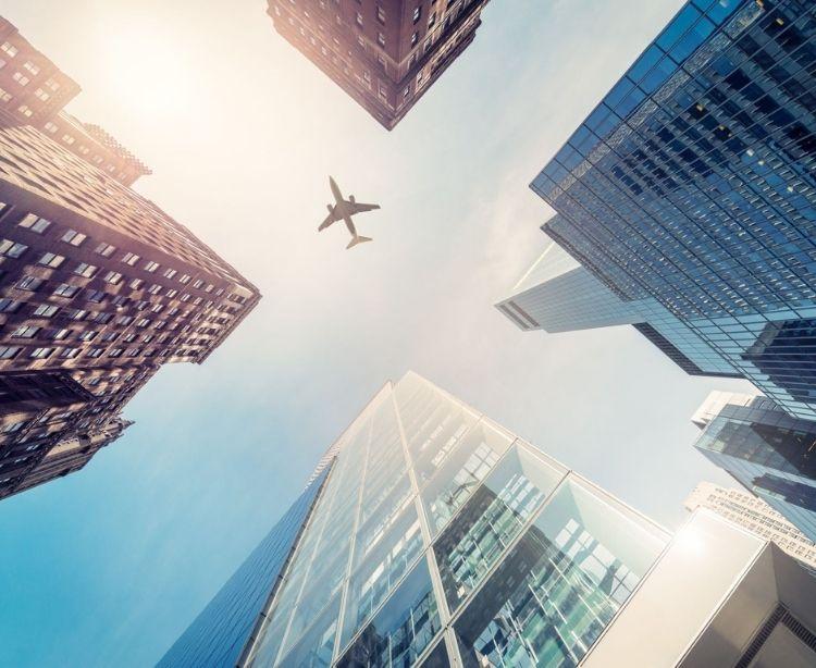 Blick von unten auf ein Flugzeug, das über Hochäuser fliegt