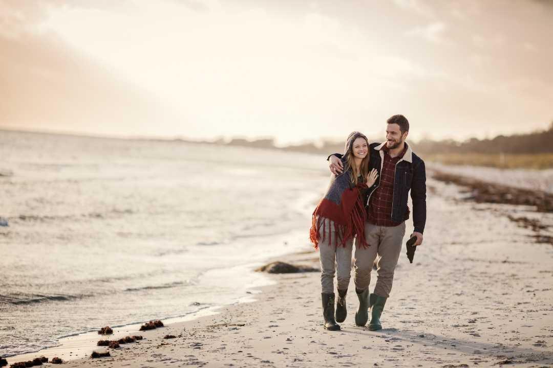 Paar spaziert am Meer im Herbst