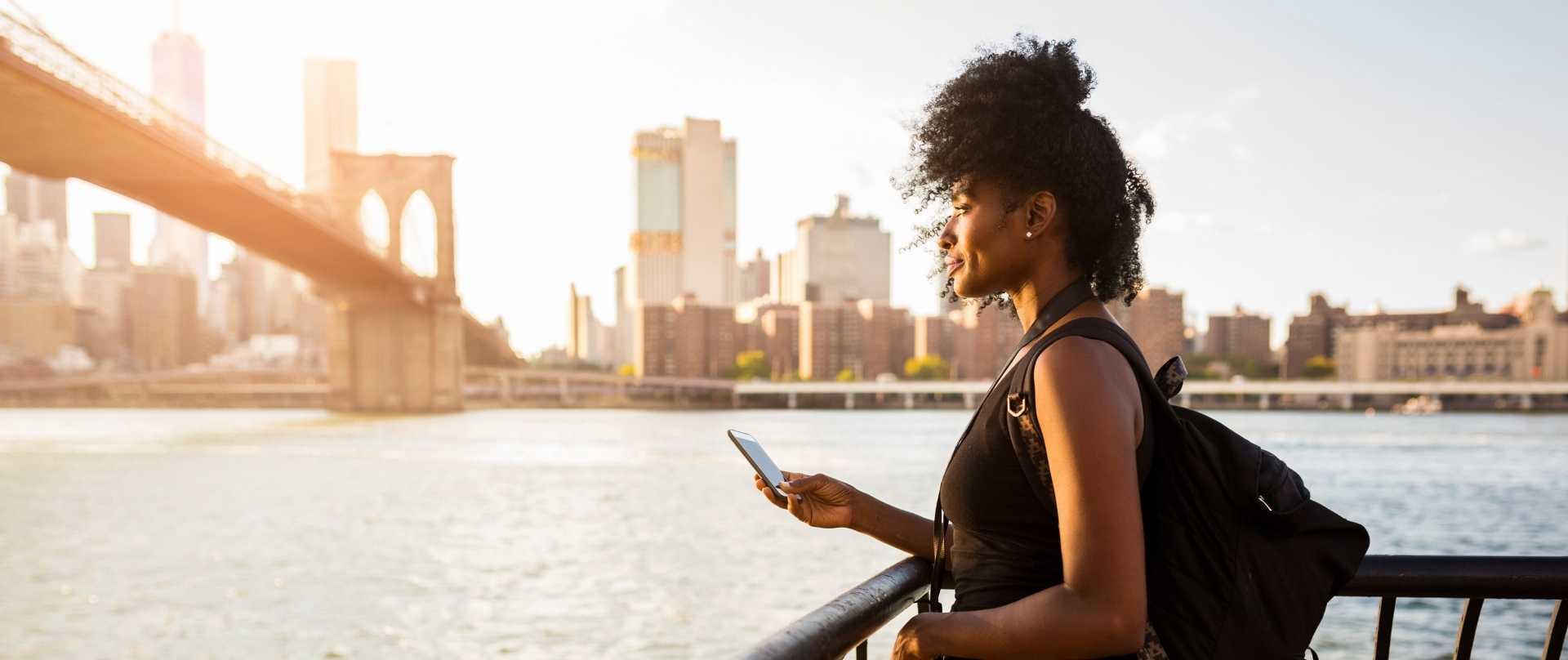 Frau mit Smartphone in New York an Brooklyn Bridge