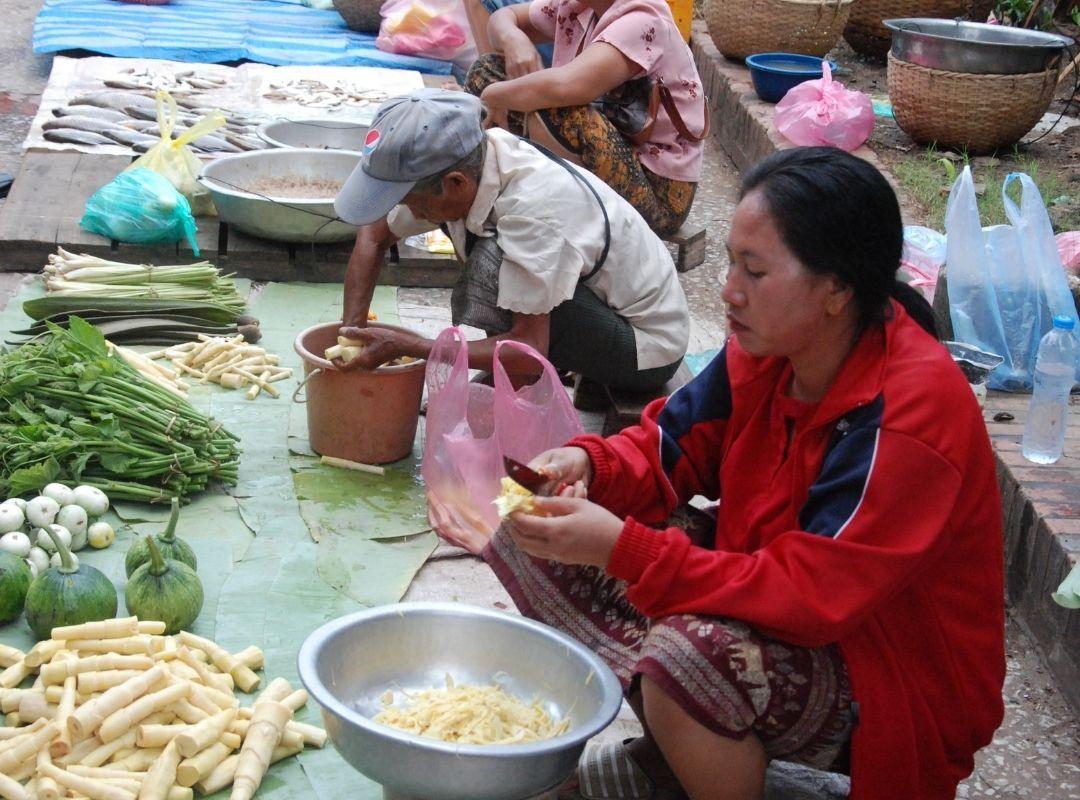 Einheimische schneidet Gemüse auf einem Markt